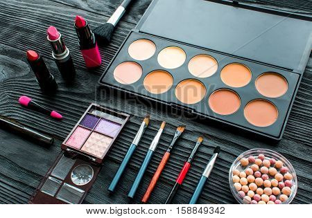 set of colorful decorative cosmetics on dark wooden background.