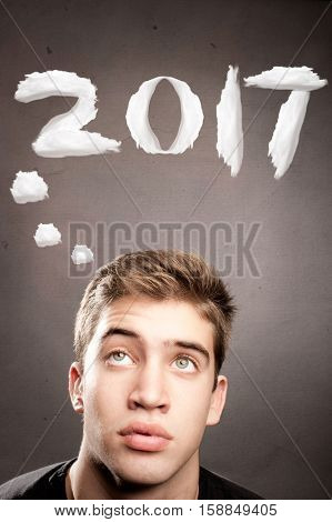 young man thinking with new year 2017 over his head