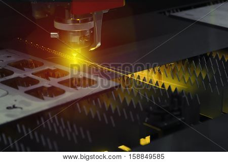 The laser cutter machine while cutting the sheet metal with the lighting effect