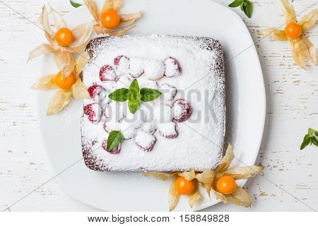 Chocolate cake with berries strawberry physalis golden barries and mint on white background. Top view