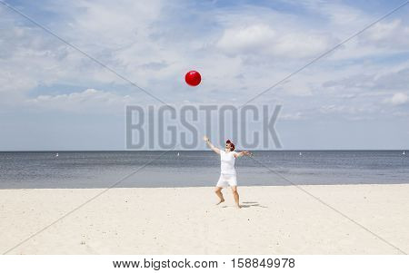 horizontal image of a caucasian woman on the beach wearing white shirt and shorts throwing a big red beach ball up in the air on a beautiful warm sunny summer day.