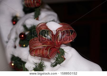 Red Christmas ribbon on a snow covered balcony