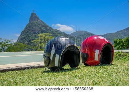 Red and black motorcycle helmets lying on the grass, Tijuca Forest, Rio de Janeiro, Brazil