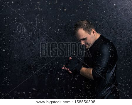 Self-motivation.Portrait of young boxer disposing himself before fight. aquastudio shot with drops