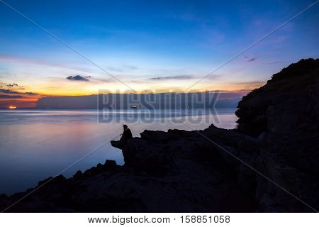 Women siting on a ledge of a mountain enjoying the beautiful sunset over a wide river valley in Thailand