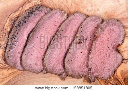 Grass fed juicy corn roast beef on olive wood cutting board