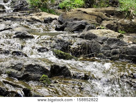 flowing stream in the middle of a riverbed and waterfall