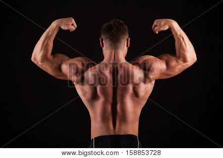 Rear view of healthy muscular young man with his arms stretched out isolated on black background.