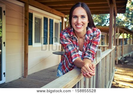 Close-up of the slim woman with tanned skin who is looking at the camera while standing on the terrace near the wooden rest house. Holding hands together in a palm