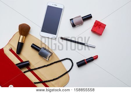 A mid shot of red colored clutch including all needs fore makeup. Phone, nail polishes, brush, red small box scattering