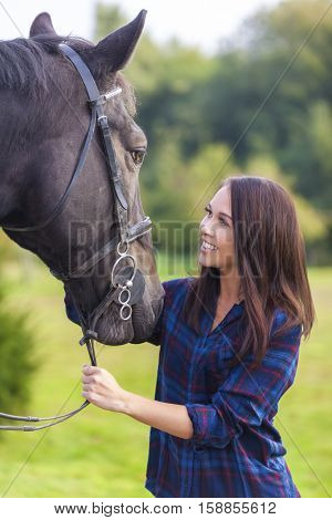 Beautiful happy smiling Asian Eurasian young woman or girl wearing plaid checked shirt with her her horse in sunshine