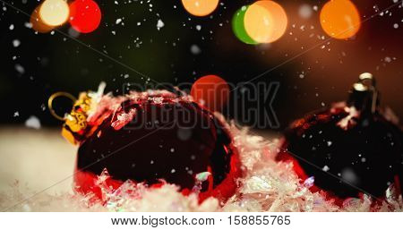 Snow falling against close-up of christmas baubles on snow