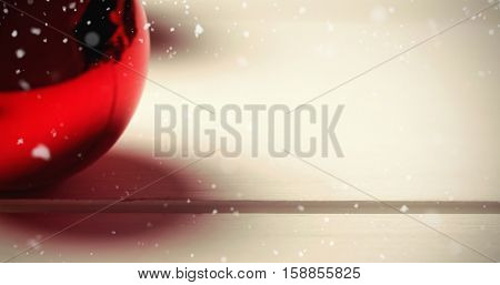 Snow falling against red christmas bauble on wooden table