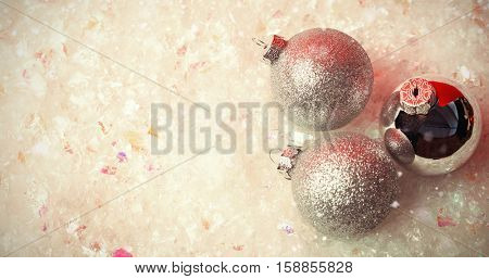 Snow falling against three christmas baubles on snow