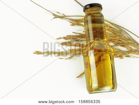 Rice bran oil in bottle glass and unmilled rice on wooden background