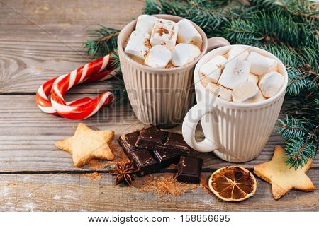Christmas hot drink. Cocoa with marshmallow, chocolate, cinnamon and spruce branches on a wooden background