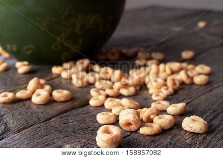 A low angle view of dry cereal spilled on a wooden table with a green cereal bowl.