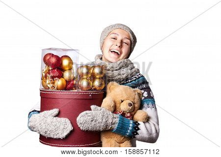 Young cute smiling girl in sweater, holding a box of Christmas decorations. Winter, Cristmastime, New Year holiday. White background, copy space