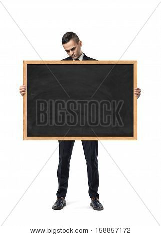 An upset businessman holds an empty blackboard isolated on the white background. Business defeat. Emotional state. Lack of fresh ideas.