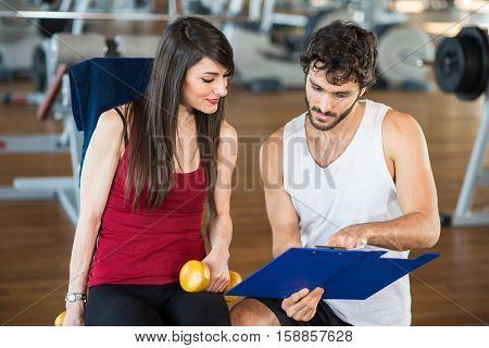 People reading a clipboard in a gym