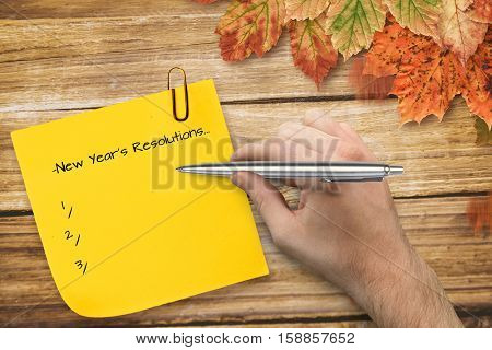 Hand holding a silver pen against composite image of sticky note with grey paperclip Sticky note with grey paperclip against autumn leaves on wood