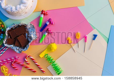 Candy, chocolate, whistles, streamers, balloons, 2017 candles on holiday table. Concept of new year. View top.