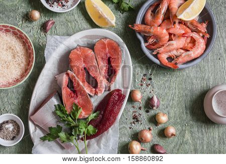 Ingredients for cooking lunch - fresh red fish shrimp rice spices. On a wooden table top view. Flat lay
