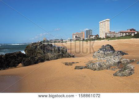 Empty Rocky Beach Against City Skyline And Blue Sky