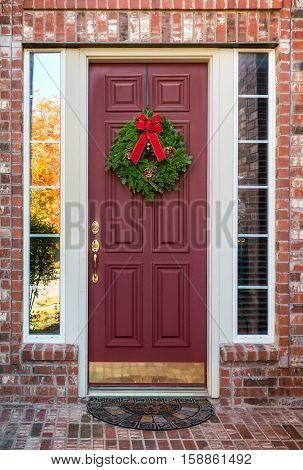 Christmas wreath hanging on a red wooden door