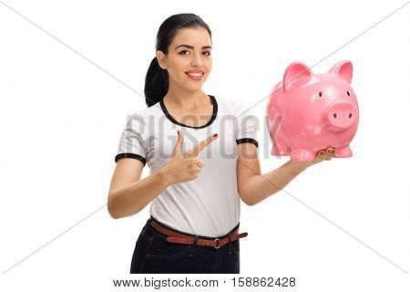 Young woman holding a piggybank and pointing isolated on white background