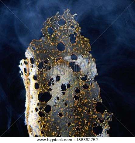 Close up detail of marijuana oil concentrate aka shatter isolated on black background with smoke
