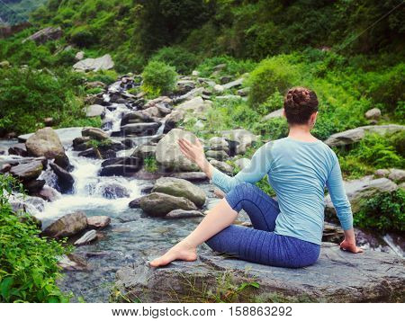 Yoga exercise outdoors -  woman doing Ardha matsyendrasanaasana asana - half spinal twist pose at tropical waterfall in Himalayas in India. Vintage retro effect filtered hipster style image.