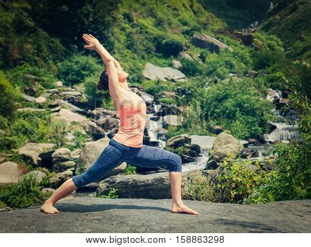 Yoga outdoors - sporty fit woman doing Ashtanga Vinyasa Yoga asana Virabhadrasana 1 Warrior pose posture at waterfall in HImalayas mountains. Vintage retro effect filtered hipster style image.