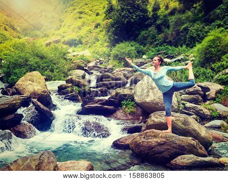 Yoga outdoors - woman doing yoga asana Natarajasana - Lord of the dance balance pose outdoors at waterfall in Himalayas. Vintage retro effect filtered hipster style image.