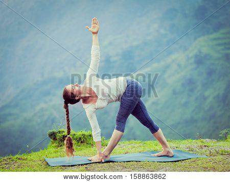 Woman doing Ashtanga Vinyasa yoga asana Parivrtta trikonasana - revolved triangle pose outdoors. Vintage retro effect filtered hipster style image.
