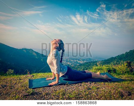 Yoga outdoors  - woman doing Ashtanga Vinyasa yoga Surya Namaskar Sun Salutation asana Urdhva Mukha Svanasana - upward facing dog pose in mountains in the morning. Vintage retro hipster style image.