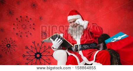 Santa reading bible with sack of christmas present beside him against red snow flake background