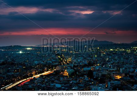 Panorama of Athens at sunset. Beautiful cityscape with seashore and distant islands visible under the red sunset sky. Travel photography.