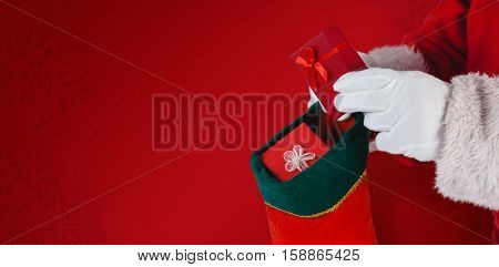 Santa Claus putting presents in Christmas stockings against red snowflake background