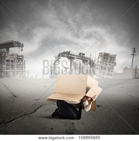 Afraid businessman is hiding under a cardboard in a city destroyed