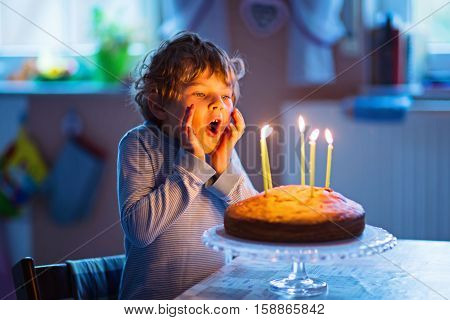 Happy little kid boy celebrating his birthday and blowing candles on homemade baked cake, indoor. Birthday party for children. Carefree childhood, anniversary, happiness. Five years old