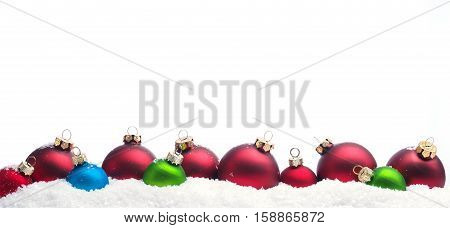Colorful Christmas baubles in row in snow on a white background
