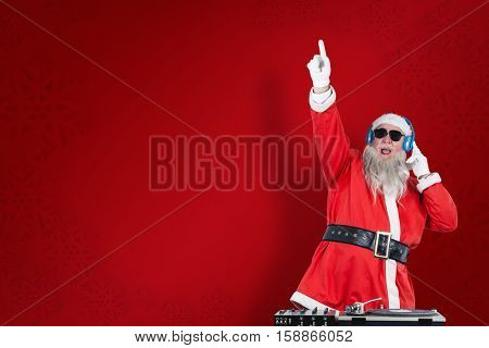 Santa Claus playing DJ with raised hand against red snowflake background