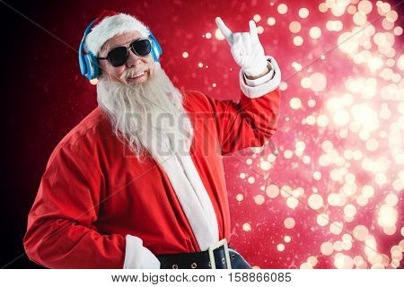 Santa Claus showing hand sign while listening to music on headphones against light design shimmering on red