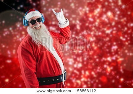 Santa claus showing hand yo sign while listening to music on headphones against white snow and stars on red