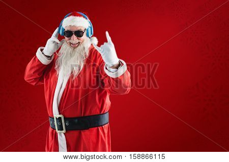 Cheerful Santa Claus showing hand sign while listening to music on headphones against red snowflake background