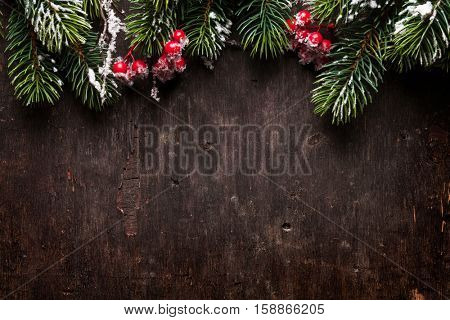 Christmas fir tree and holly berries over old wooden texture background. Top view with copy space for your greetings