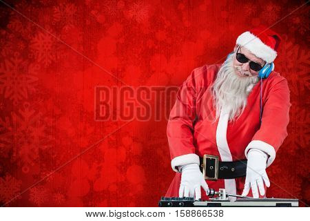DJ Santa Claus mixing sound against red paint splatter background