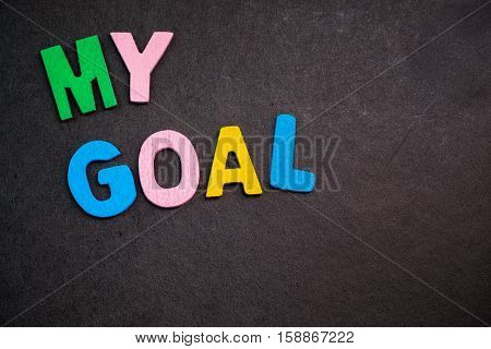 """Colorful wooden letters forming the phrase """"my goal""""."""