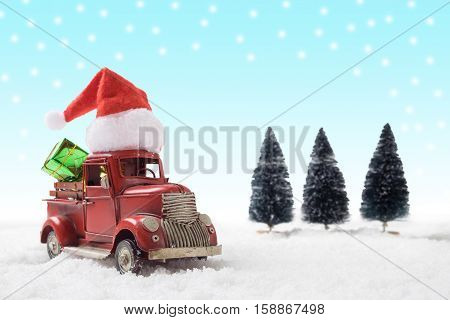 Christmas toy santa truck with gift boxes and pine tree on snow background.